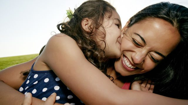 Kid kissing her mom on the cheek while mom is smiling with bright white teeth