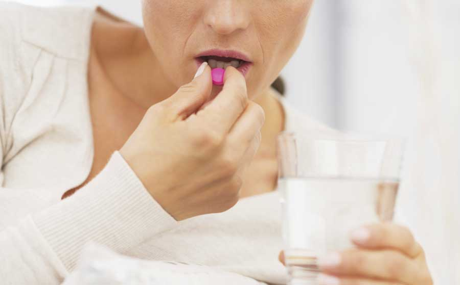 woman taking a pink pill with a glass of water.