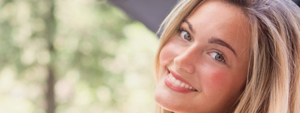 Smiling blonde girl with green eyes and bright white smile