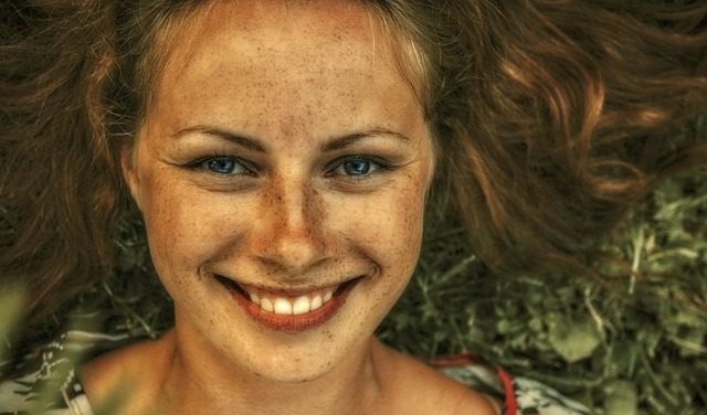 Red haired woman with lots of freckles and blue eyes smiling at the camera with green leaves in the background.