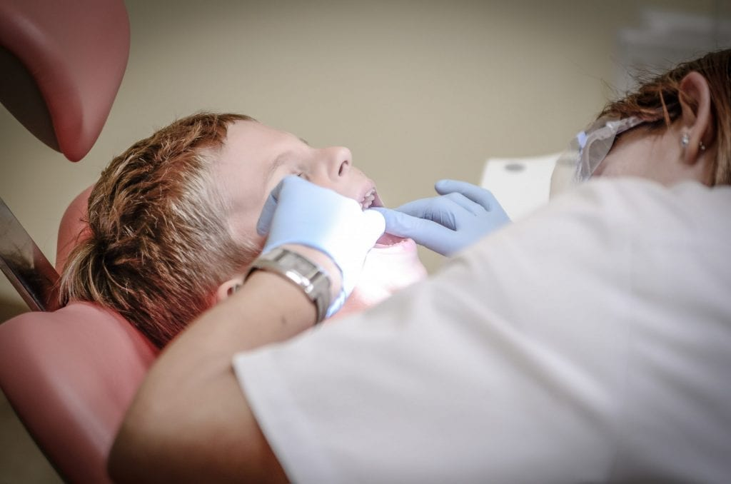 dentist working on a little boy's teeth.