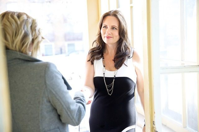 business woman shaking hands with a potential client, she's smiling