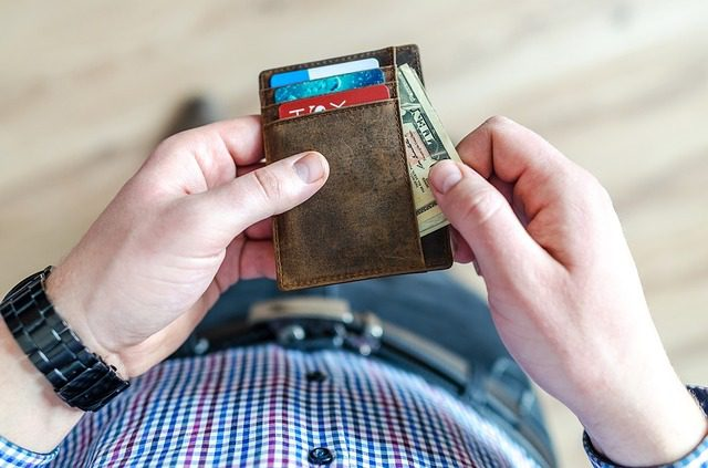 man holding a wallet with cards and money in it as he pulls money out
