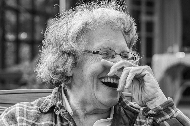 older woman with a beautiful smile laughing while wiping her nose. Black and white photo