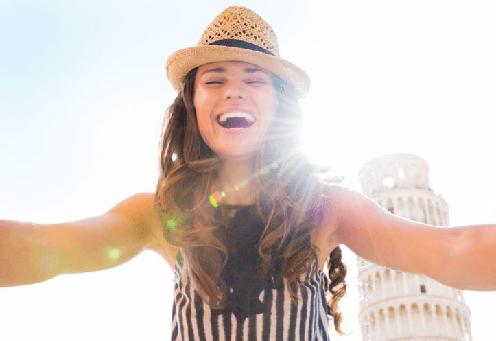 girl with bright white teeth standing in front of the leaning tower of pisa with the sun behind her