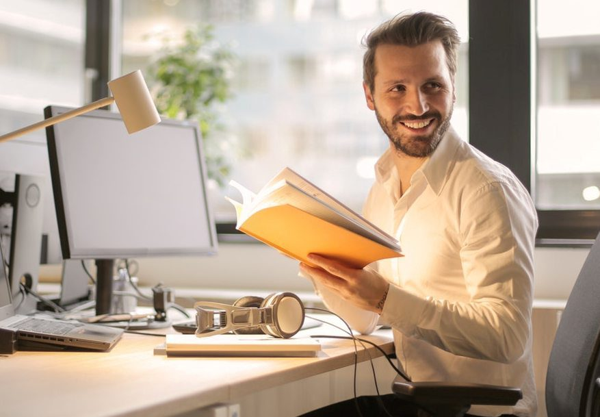 business man reading a book at desk, and looking off camera smiling
