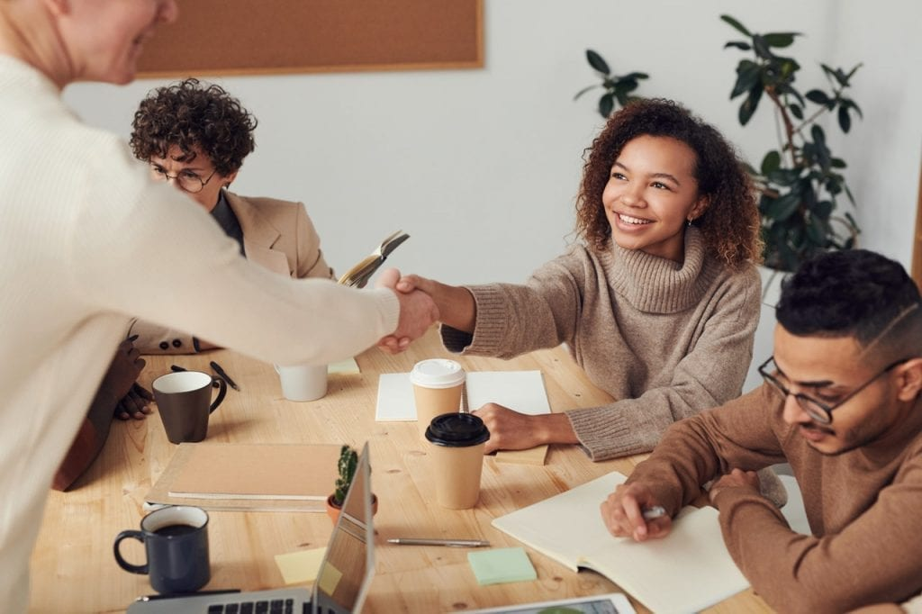 business meeting setting with a diverse group. The focus is on a black woman smiling with confidence shaking a man's hand across the table. The table has computers, coffee mugs, and papers on it.