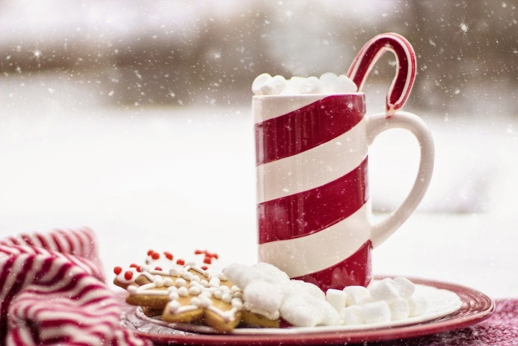 christmas cookies with a hot cocoa mug marshmallows, and a candy cane with snow falling around