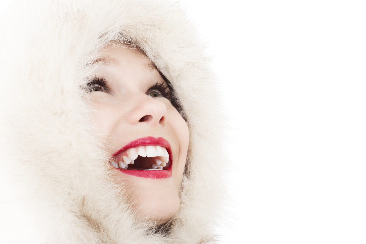 Woman on a white backdrop wearing a white fur lined coat with a hood. She's looking up in joy, and smiling. Her teeth are white which is highlighted by her red lips.