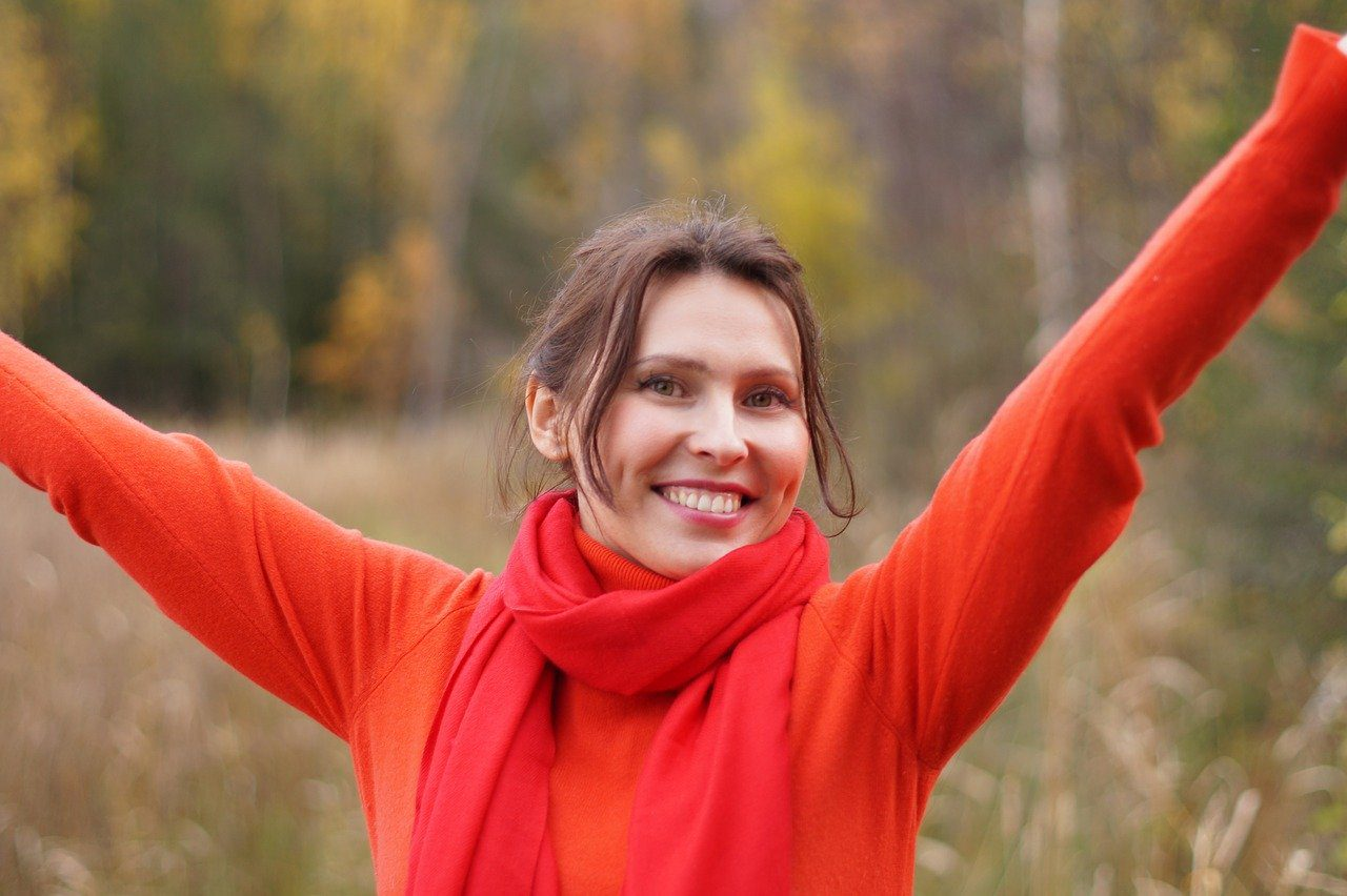 Brunette woman smiling with dimples in a red sweater and scarf, arms spread wide in a fall setting