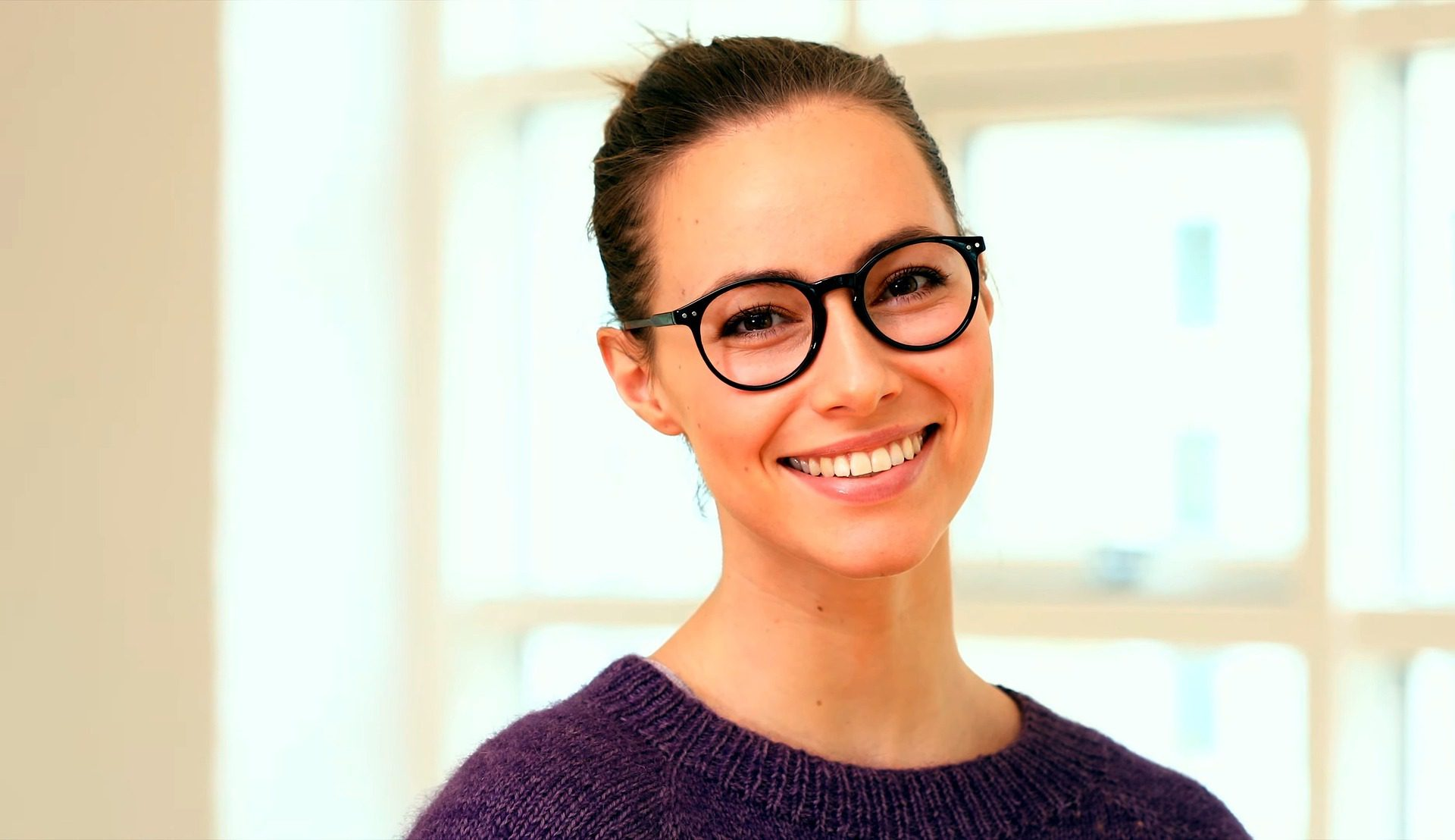 Brunette woman wearing black rim circle glasses with white teeth smiling at the camera in front of a window in a white room