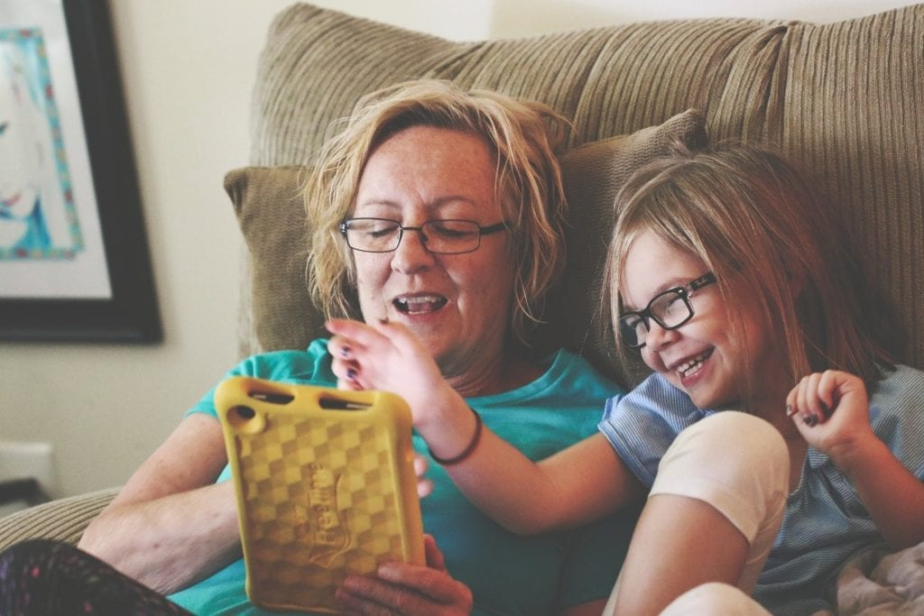 White grandma holding a kindle with laughing granddaughter. Both smiling. In living room on a couch together.