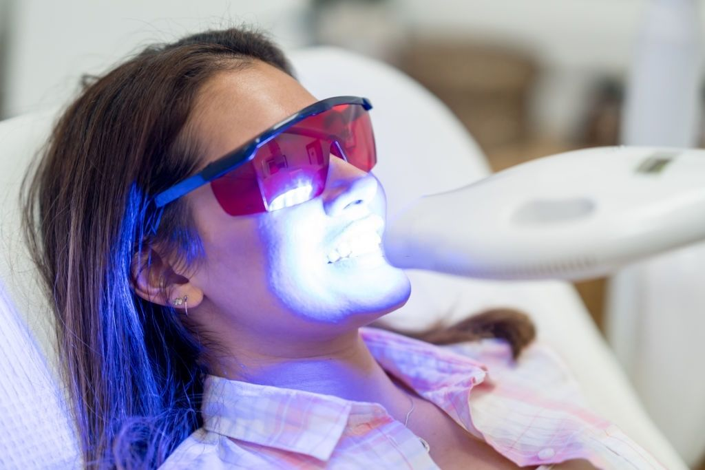 Beautiful woman getting laser teeth whitening - oral healthcare concepts